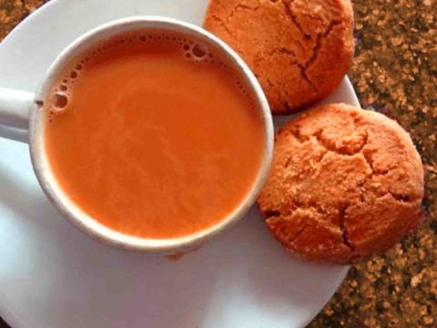 Irani Tea In A Cup With Saucer And 2 Cookies On Table